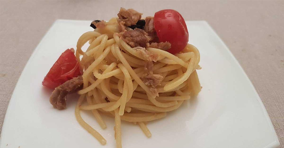 spaghetti con tonno, pomodoro, capperi e olive nere