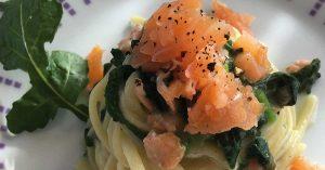 un piatto di linguine con rucola e salmone