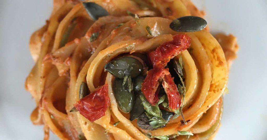 un piatto di pasta con pomodoro secco e semi di zucca